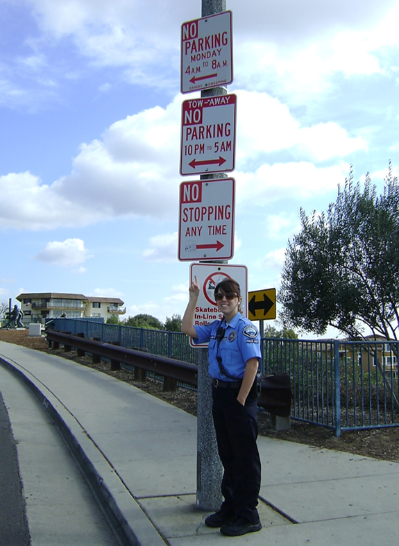 Officer pointing to three no parking signs on a lamp post