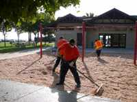 Men grating sand in front of building