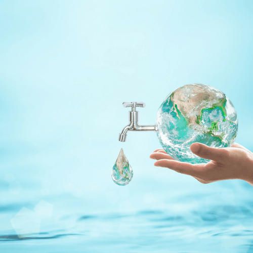 Person holding an Earth with a faucet dripping water