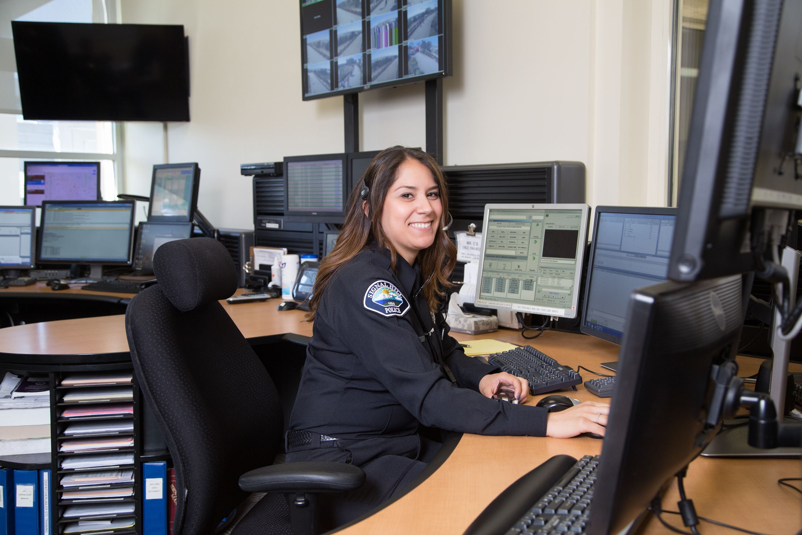 Smiling police dispatcher at a desk with a headset on