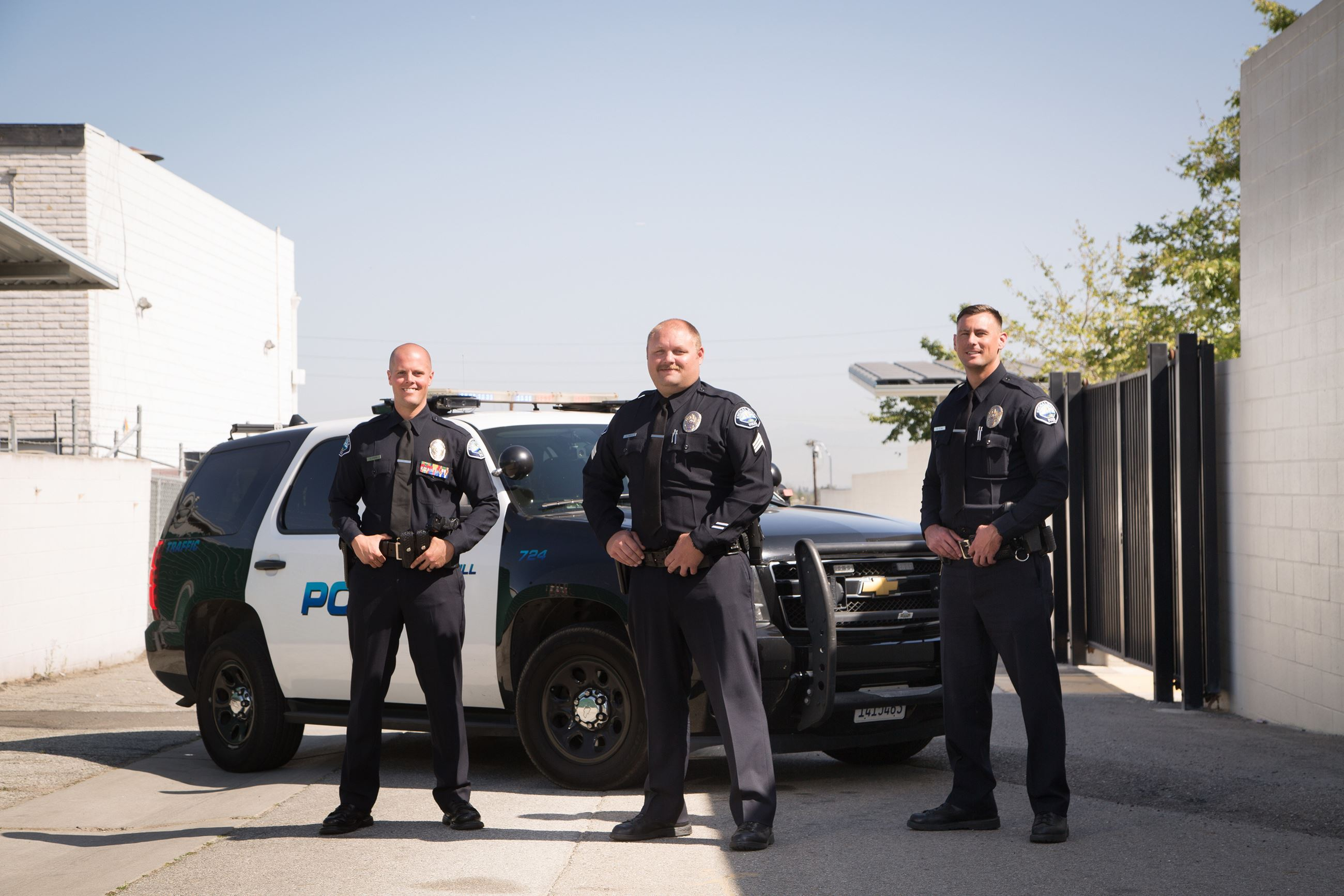 Three Signal Hill PD Traffic Officers standing by their patrol car