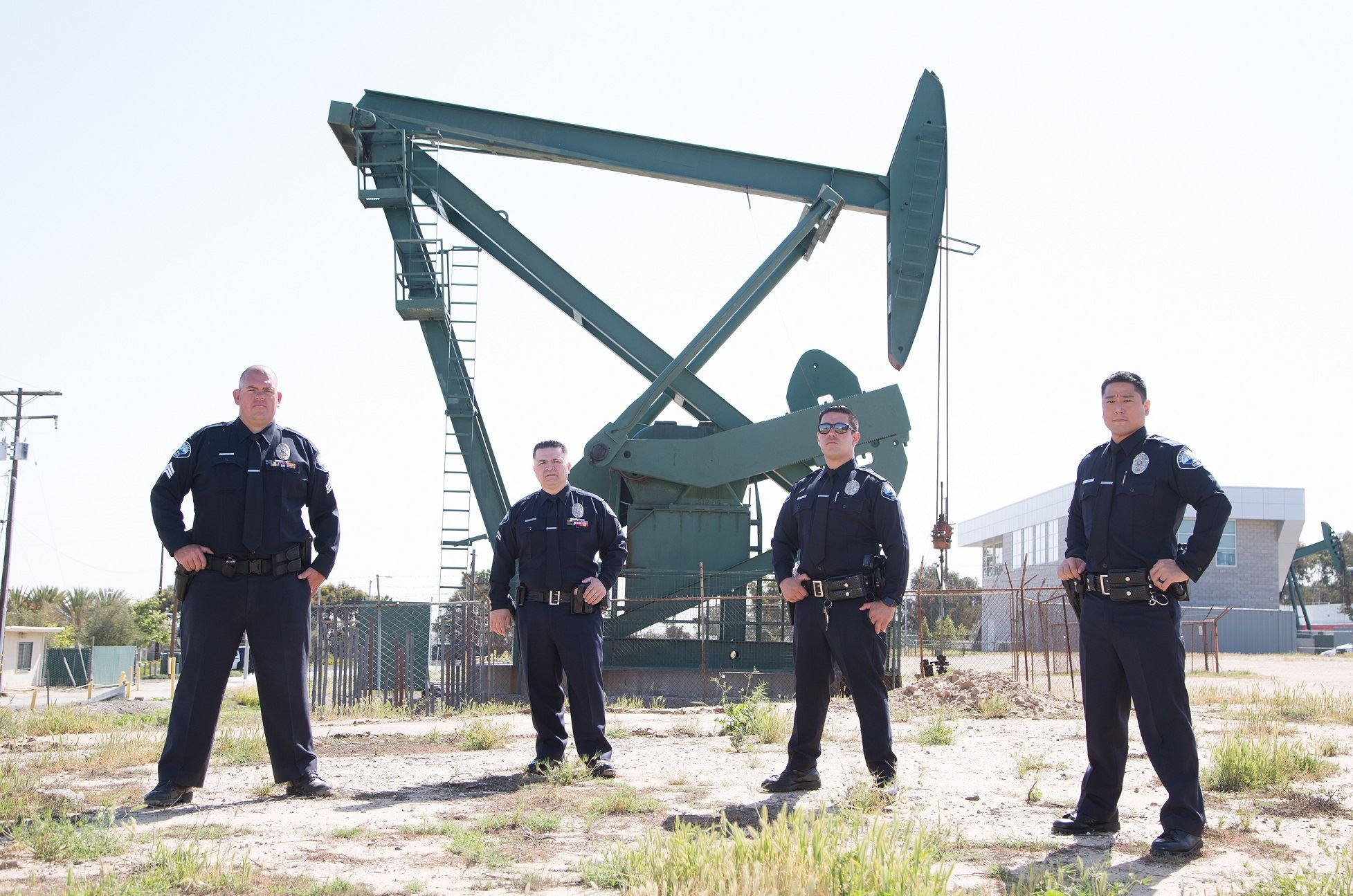 Officers standing outside in front of oil well