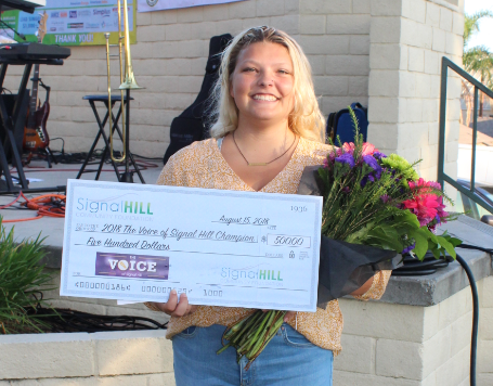 Grace Thomas holding a check for $500 and flowers after winning the Voice competition